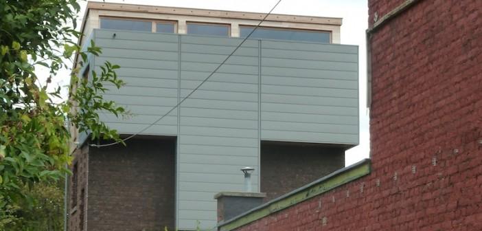 Rehausse d'une habitation avec toiture cintrée et bardage en zinc